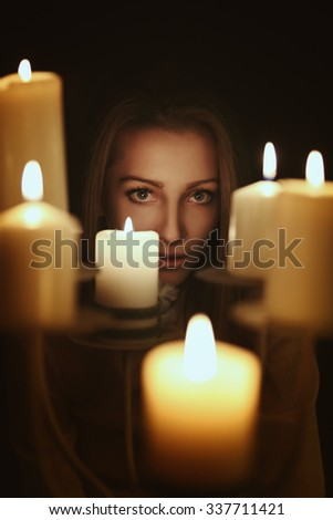 Dark candlelight portrait of a young woman . Gothic and surreal concept