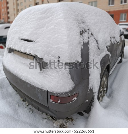 Dark car covered with snow after heavy snowfall in a winter