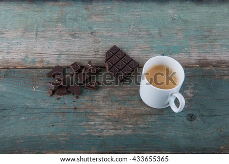 Dark chocolate and a cup of coffee on old, vintage table, stock photo