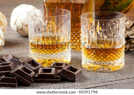 Dark chocolate and fine bourbon whiskey in crystal bottle and tumbler glasses with stylish spheres and antique globe in background