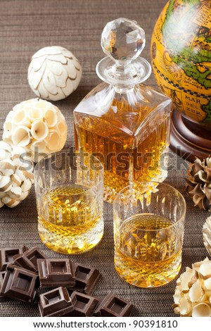 Dark chocolate and fine whiskey in crystal bottle and tumbler glasses with stylish spheres and antique globe in background - stock photo
