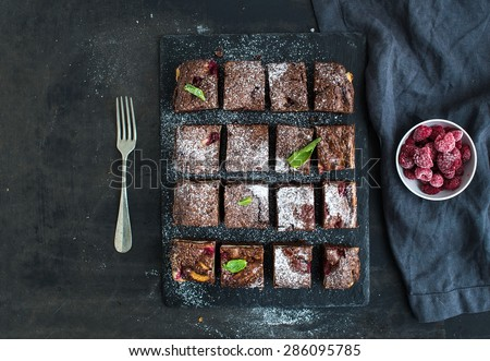 Dark chocolate and raspberry brownie squares on black stone board over black grunge background, top view, copy space - stock photo