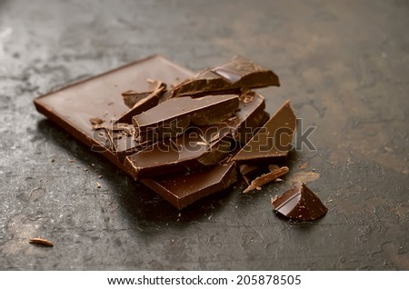 Dark chocolate bar crushed on a vintage background - stock photo