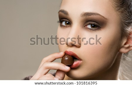 Dark chocolate beauty, portrait of a beautiful brunette with bonbons. - stock photo