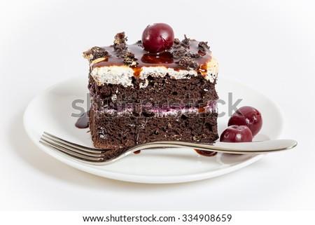 Dark chocolate cake with sweet cherry on plate, white background - stock photo