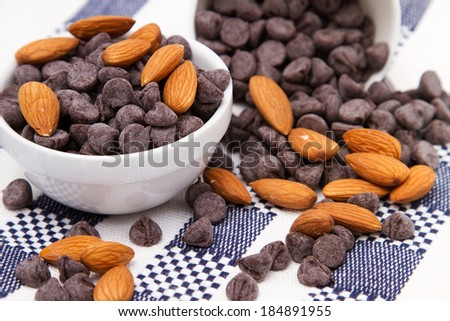 Dark chocolate chips and almonds on checkered tablecloth