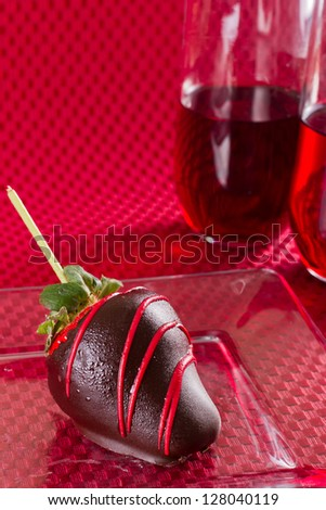 dark chocolate covered strawberry on a red background - stock photo