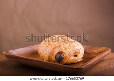 Dark chocolate croissant on a wooden plate. - stock photo