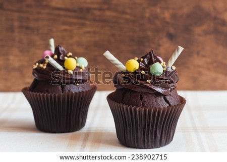 Dark chocolate cupcakes on rustic wooden background - stock photo