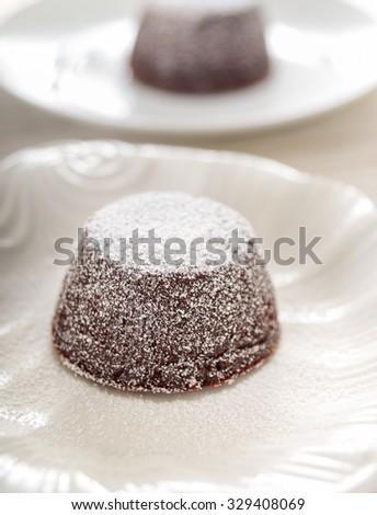 Dark chocolate lava cake on elegant white ceramic dish - stock photo