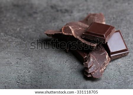 Dark chocolate pieces on  dark gray background - stock photo
