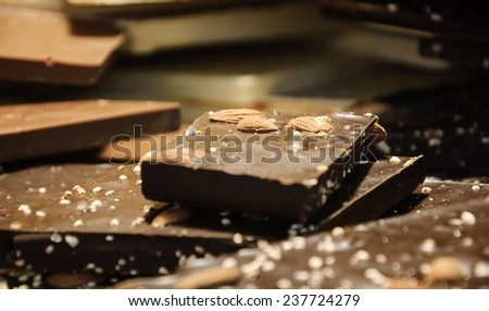 Dark chocolate with almonds. Milk and white chocolate at background. - stock photo