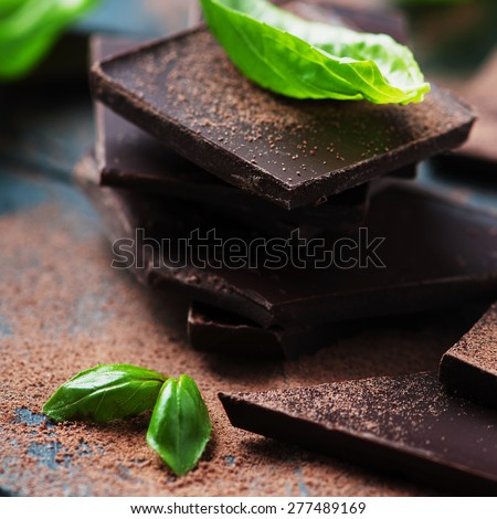 Dark chocolate with basil on the wooden table, selective focus and square image - stock photo
