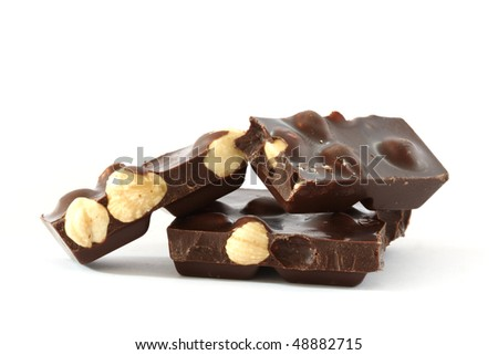 Dark chocolate with whole hazelnuts close up on white background - stock photo