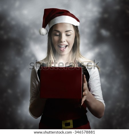 Dark christmas night concept of a beautiful christmas present girl opening a magic gift box. Miracles on xmas eve - stock photo