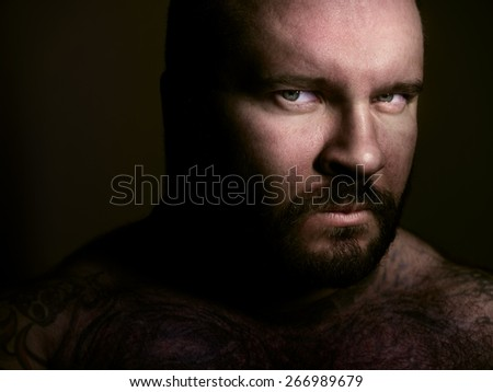 Dark closeup portrait of a bearded man - stock photo