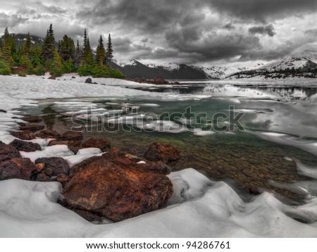 Dark clouds above almost frozen mountain lake shore - stock photo