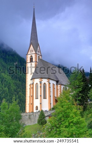 Dark clouds above St Vincent church in Heiligenblut, Austria