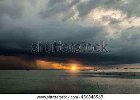 Dark clouds and rainstorm with sunset at the lake, un-focus image.