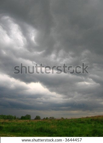dark clouds coming, city wait... to... ,  Nimbostratus clouds and meadow,  latin: Nimbostratus - stock photo