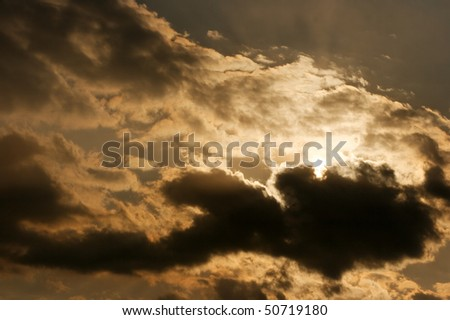 Dark clouds covering the sun in the sky - stock photo