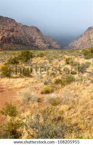 Dark clouds loom between mountain peaks at Red Rock Canyon National Conservation Area in Nevada - stock photo