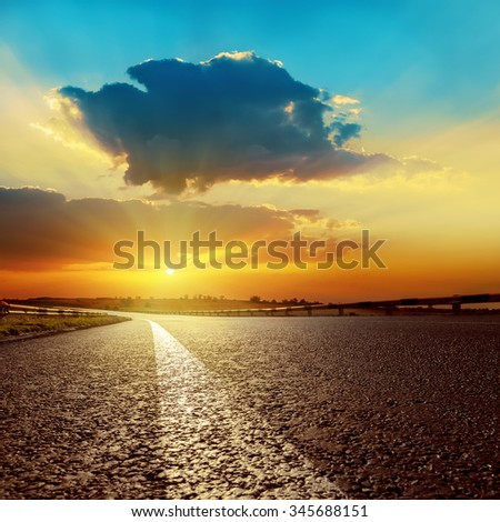 dark clouds over asphalt road on sunset - stock photo