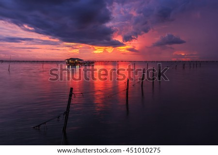 Dark clouds over lake with red sky and wooden hut on surface at sunset