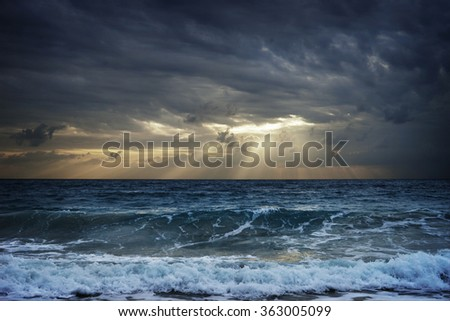 Dark clouds over stormy sea hiding sunlight in Thailand. - stock photo