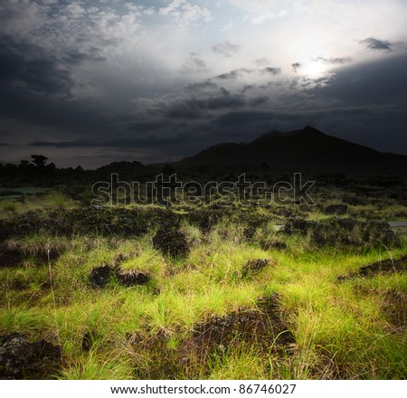 Dark clouds over volcanic valley with grass and rocks. Mountain Agung in Bali. Indonesia - stock photo
