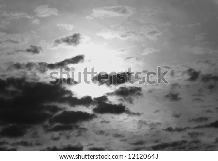 Dark clouds shroud a brilliant sun in this black and white sky background - stock photo