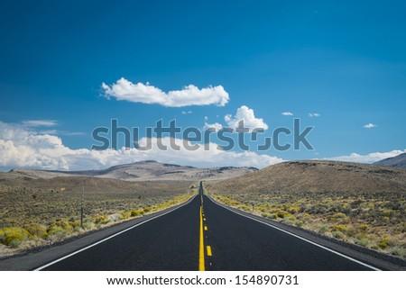 Dark clouds threatening a rain storm above desert highway - stock photo