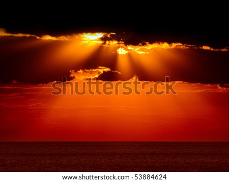 Dark clouds with sun rays over sea. - stock photo