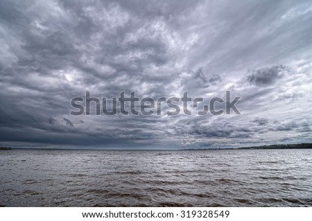 Dark cloudy sky on the Volga River - stock photo
