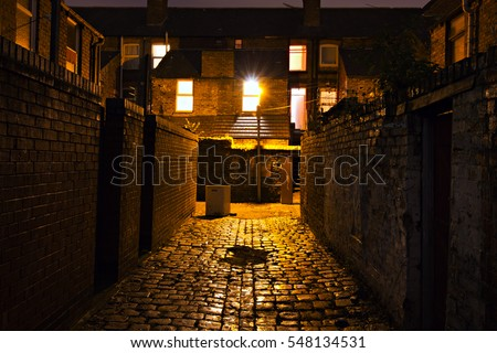 Dark cobblestoned alley at night in the back streets of Liverpool UK
