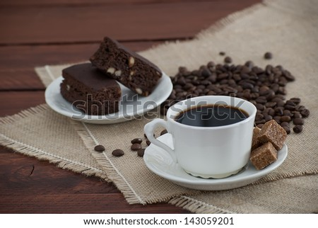 dark coffee with brown sugar cubes, the bottom plate of chocolate brownies on the wooden table decorated with burlap coffee beans