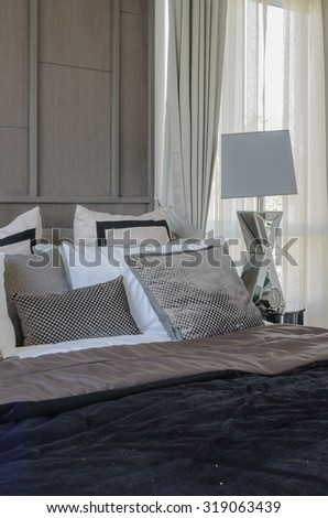 dark color scheme modern bedroom design with pillows on bed