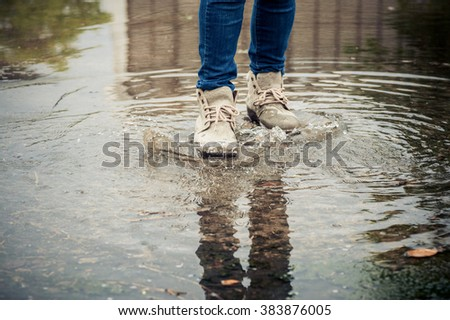 Dark color tone. Traveler female shoe walk on water on concrete floor after heavy raining.