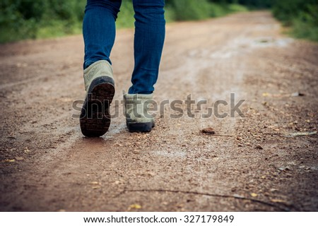 Dark color tone. Woman traveler in boot walk on the wet dirty road in urban forest.