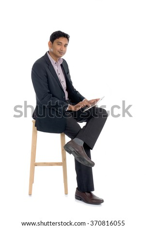 dark complexion business man using tablet while sitting - stock photo