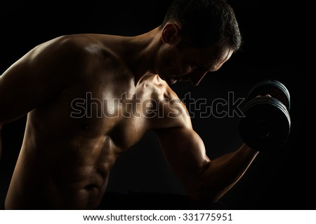 Dark contrast brutal silhouette of young muscular fitness man. Bodybuilder with beads of sweat training in gym. Working out with dumbbells on black background