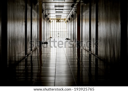 Dark corridor and light at destination - stock photo