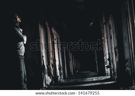 dark corridor and the man in a gloom - stock photo