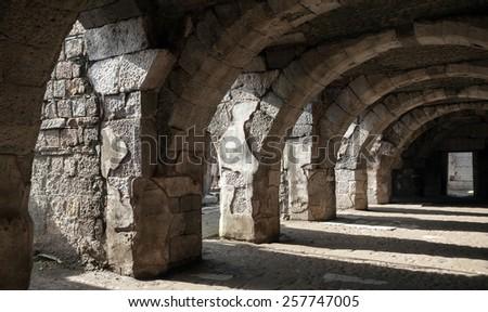 Dark corridor interior with arcs. Ruins of Ancient city Smyrna. Izmir, Turkey - stock photo
