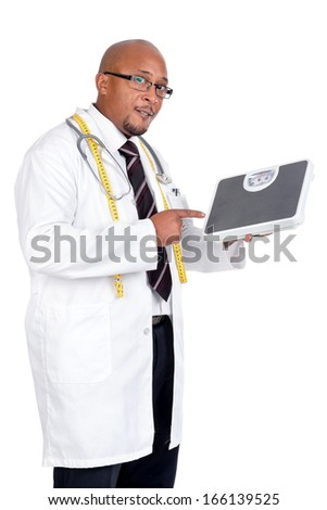 Dark doctor posing with weight scale and measuring tape - stock photo