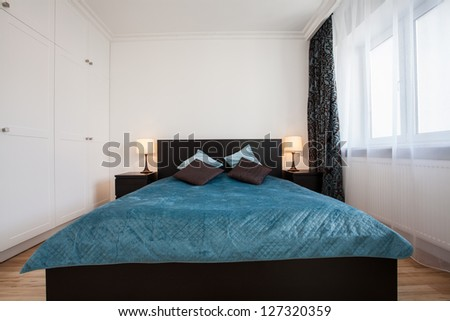 Dark double bed in a modern bedroom interior - stock photo