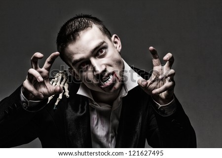 Dark dramatic portrait of the real young vampire - stock photo