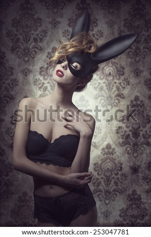 Dark easter portrait of sensual curly woman with romantic expression posing with mysterious bunny mask and lace lingerie  - stock photo