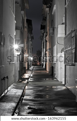 Dark empty back alleyway after the rain - stock photo