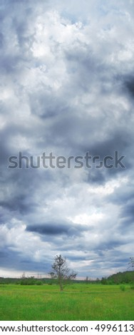 Dark foreboding clouds are spread across a late afternoon sky - stock photo